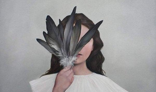 鳥の羽で顔を隠す女性