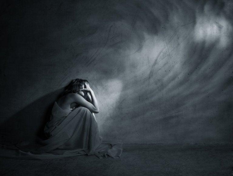 暗い中でうずくまる女性