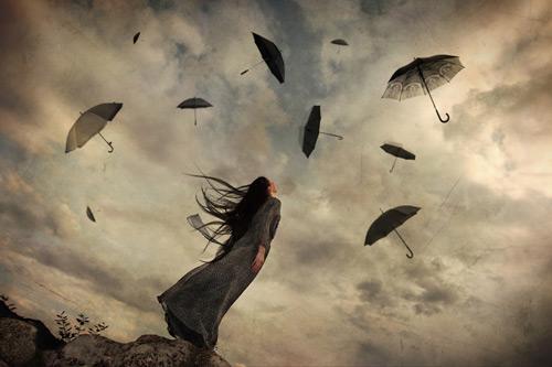 空に舞う黒い傘を見上げる女性