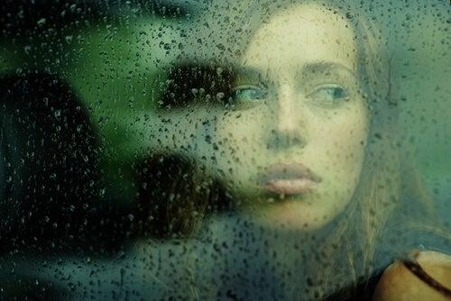 雨の窓の外を眺める女性