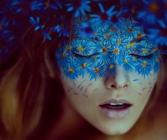 顔に青い花が映る女性