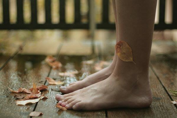 裸足の足と落ち葉