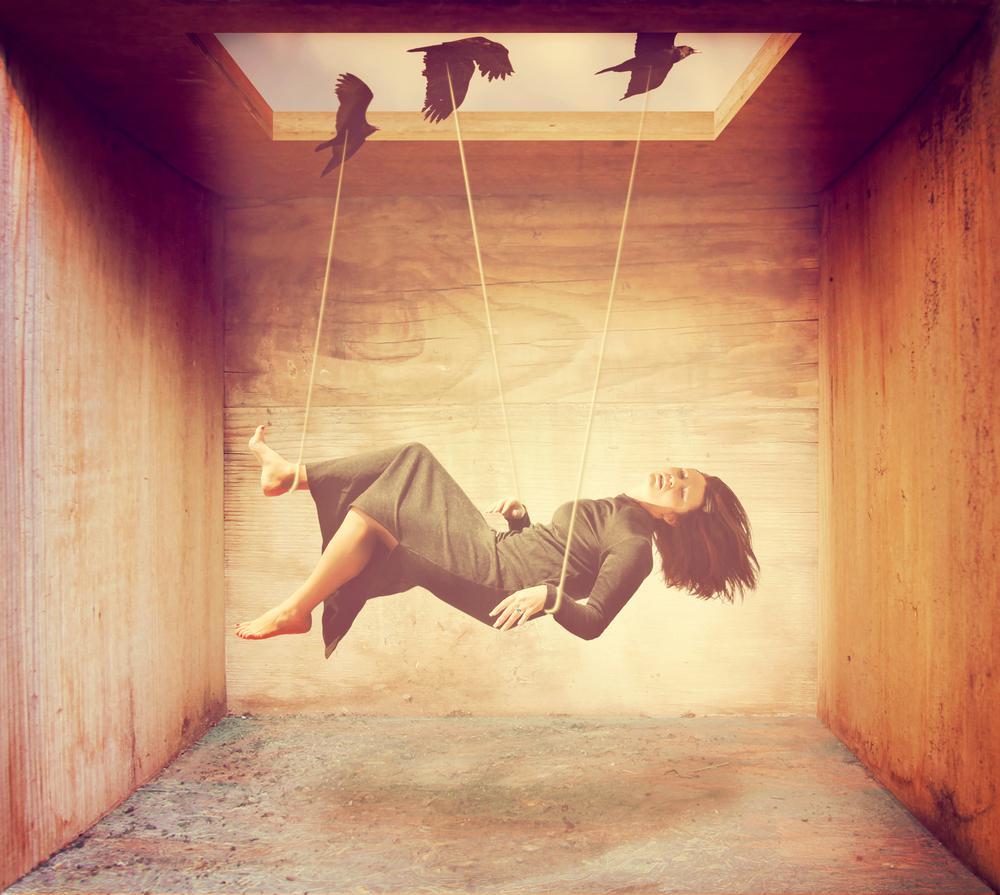 鳥に縄でつられる女性