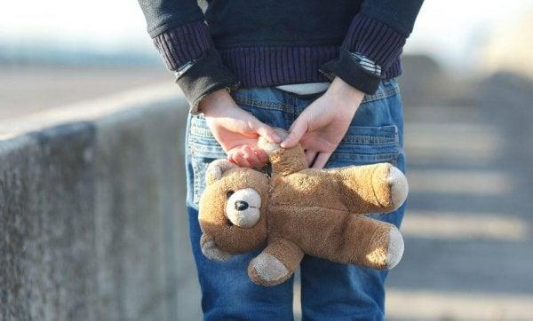 クマのぬいぐるみを後ろ手に持つ