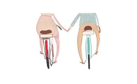 自転車に乗って手をつなぐ二人
