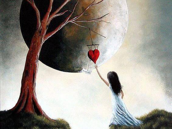 木にぶら下がるハートに手を伸ばす少女