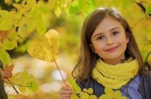 笑顔でハート型の落ち葉を手にする少女