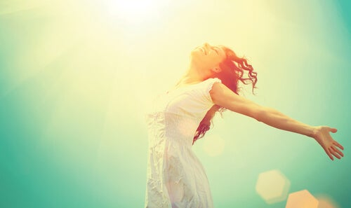 太陽に手を広げる女性