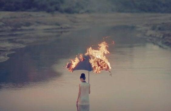 燃える傘をさす女性