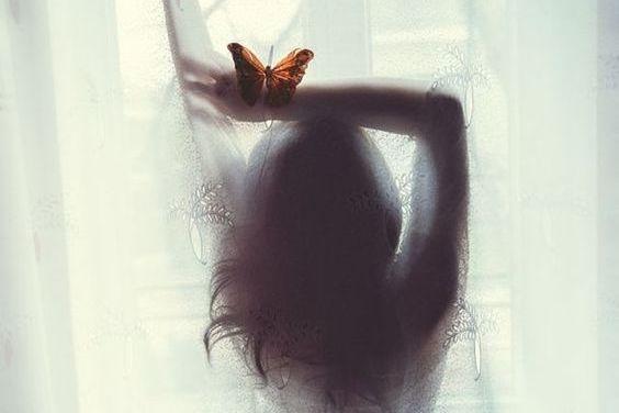 女性の影にとまる蝶
