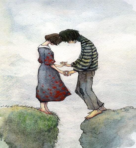 崖の割れ目を挟んで手をつなぐ二人