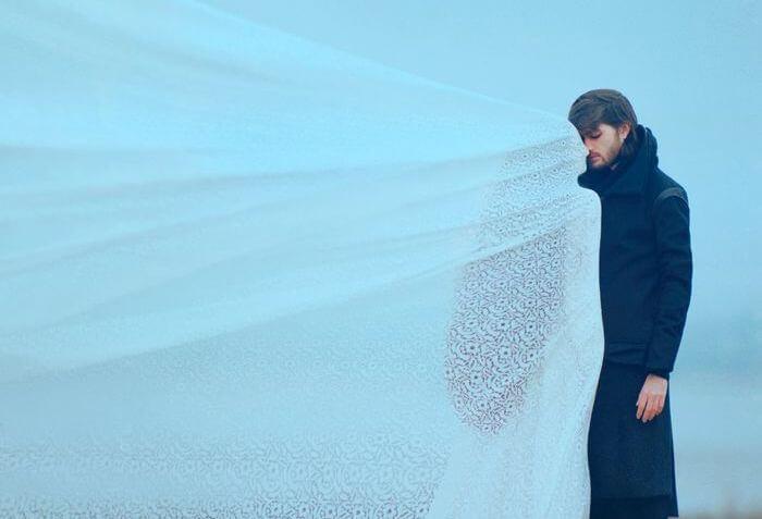 白いベールに包まれた女性の前に立つ男性