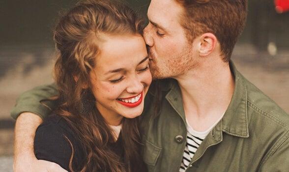 彼女の頭にキスする男性
