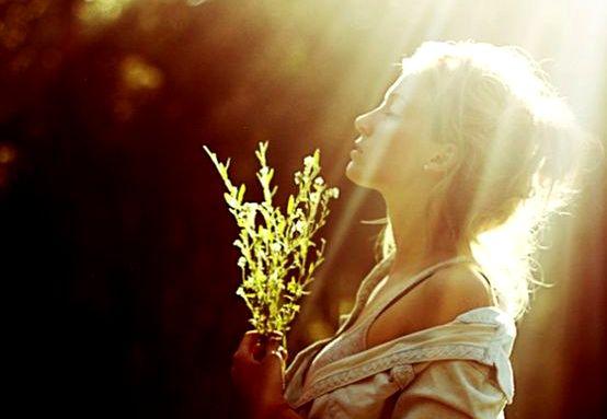 手に草を持った日の中の女性