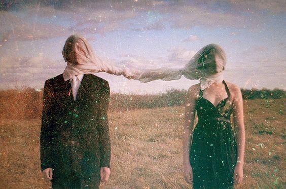 布で覆った顔を結びつける二人