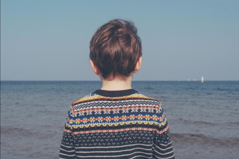 海を眺める子供の後ろ姿