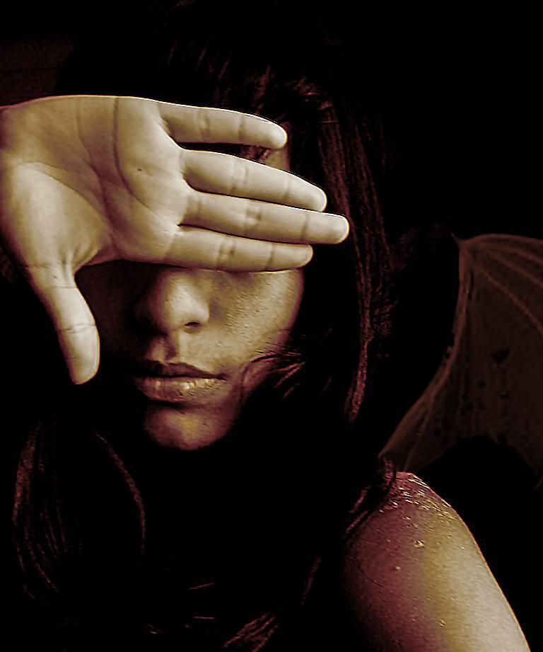 手で目を隠す女性