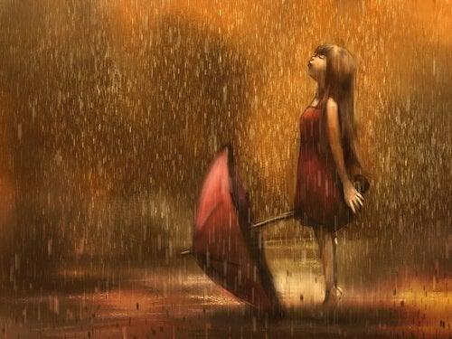 傘を置いて雨に濡れる少女