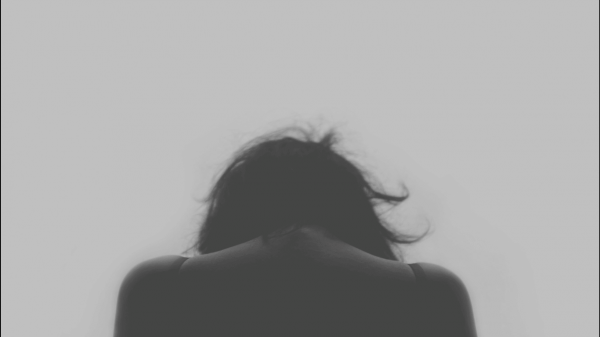 頭をもたげる女性の後ろ姿
