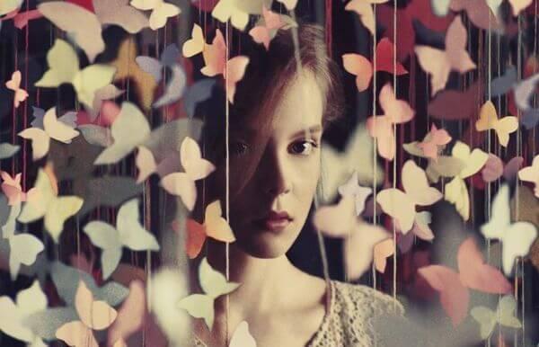 蝶のカーテンの間に立つ女性