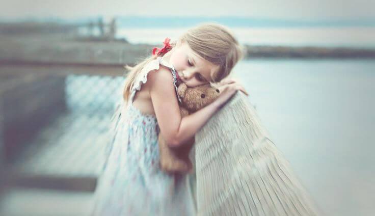 クマのぬいぐるみを抱きしめる水辺の少女