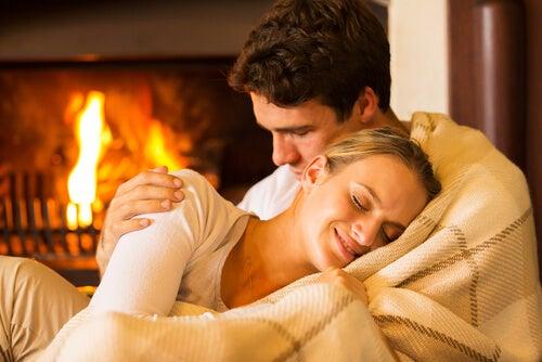 暖炉の前で抱き合うカップル
