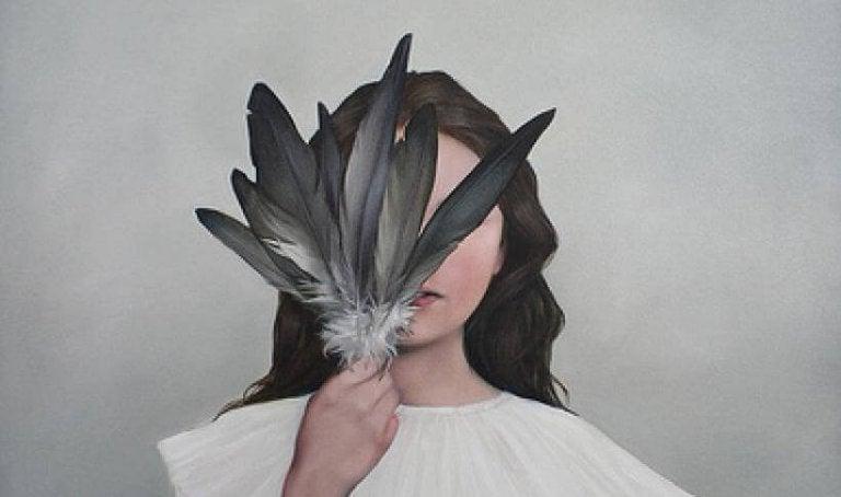 黒い羽根で顔を隠す女性
