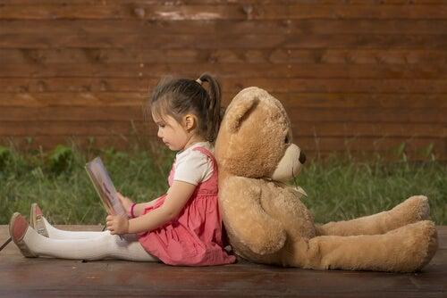 クマのぬいぐるみと背中合わせの少女