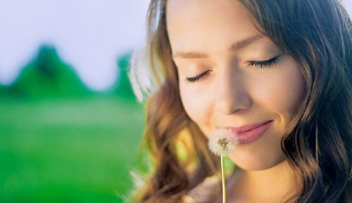タンポポの綿毛を顔に近づける女性