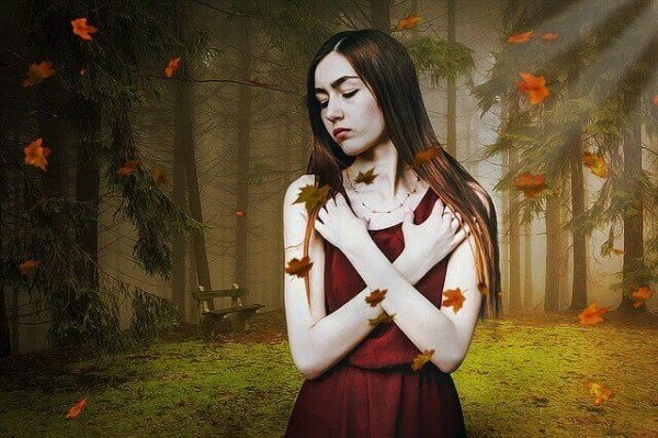 落ち葉の舞う森の女性