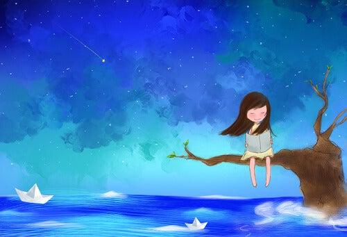 海に突き出す木の上で本を読む少女
