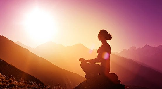山の上で瞑想する女性