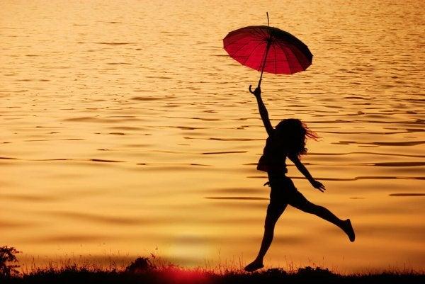 傘を持って水辺で踊る