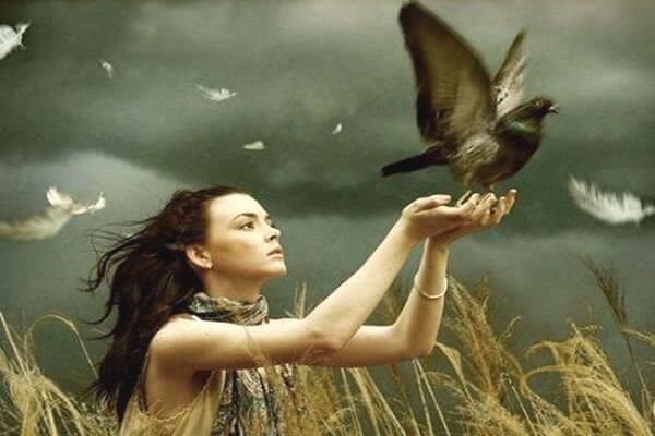鳩を手に乗せる女性