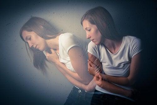 自分の肩を抱く二重の女性