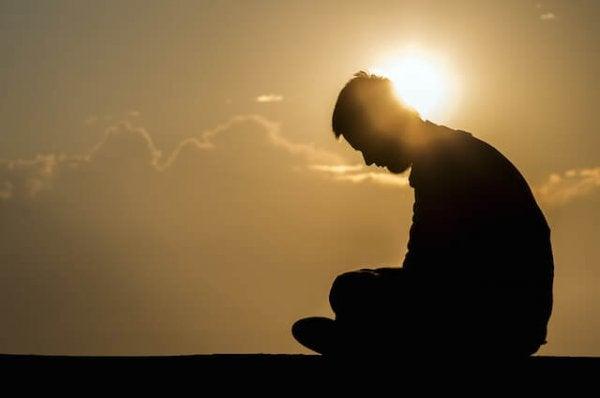 日の出と座る男性の影