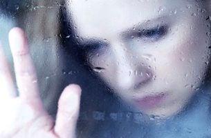 窓ガラスに手をつく女性
