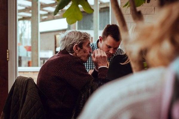 高齢の父と食事する息子