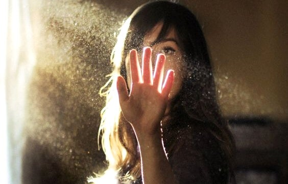 日の光に手をかざす女性