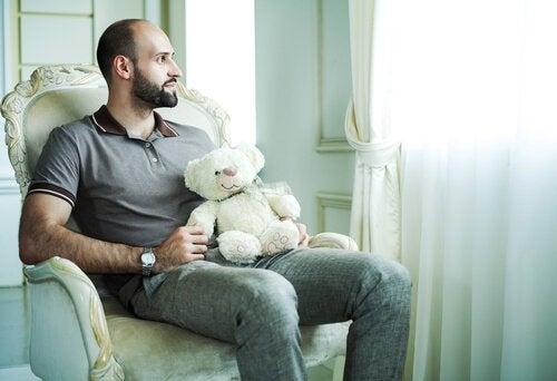 テディベアを持って座る男性