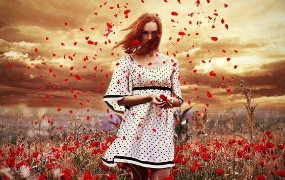 赤い花に囲まれた女性