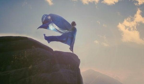 崖っぷちに立つ青いドレスの女性