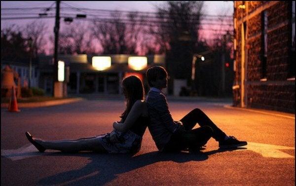 道に座る若いカップル