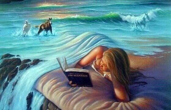 海のシーツのベッドで本を読む女性