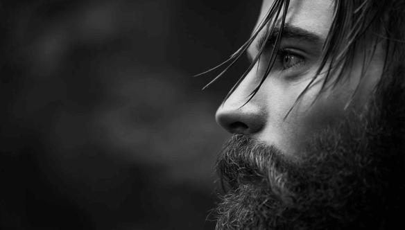 前を見つめる髭の男性
