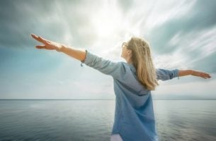 海辺で手を広げる女性