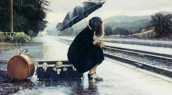 雨の中電車を待つ
