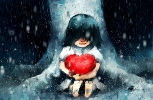 雨の中ハートを抱いて座る少女