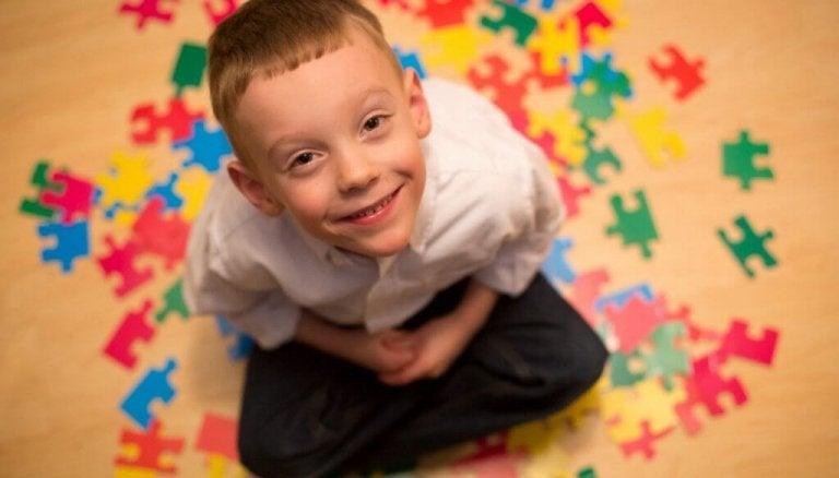 自閉症の子供がパズルの上で笑う