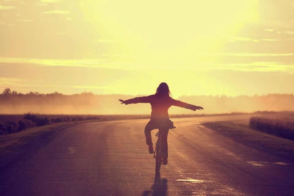自転車を手放し運転する女性と夕日